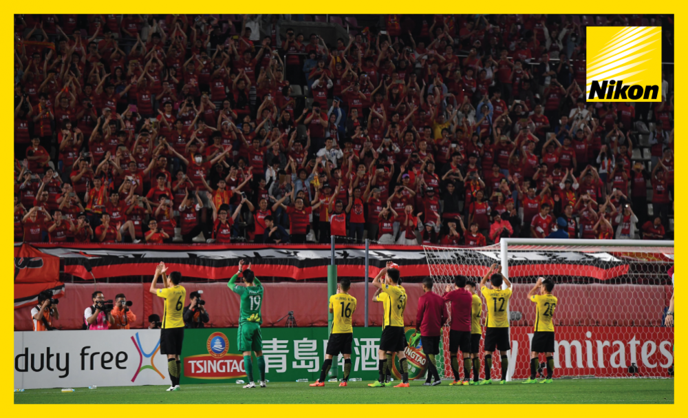 Guangzhou Evergrande players celebrate with their massed ranks of travelling fans after Tuesday's 2-1 defeat at Kashima Antlers was enough to reach the AFC Champions League quarter-finals via the away goals rule.
