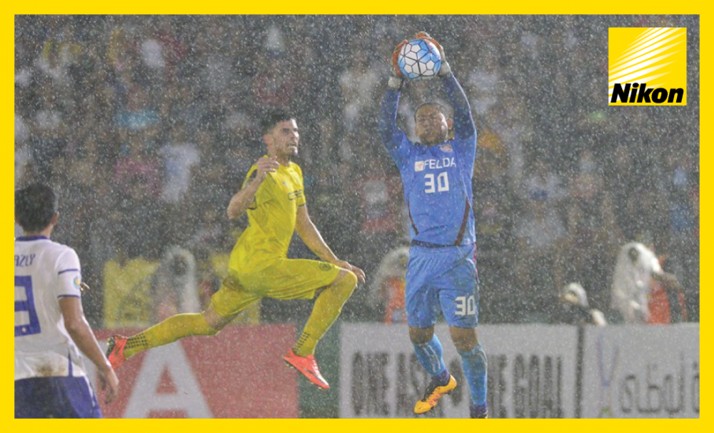 Wet And Windy: Felda United goalkeeper Farizal Harun attempts to catch in tricky conditions in AFC Cup Group G encounter with Felda United on Wednesday.​